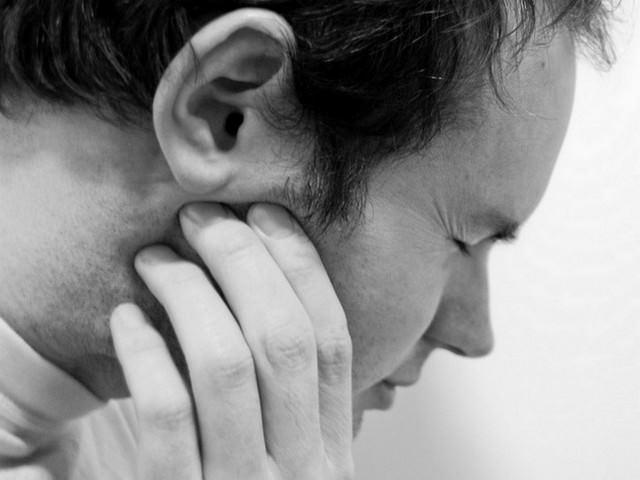 Мужчина хмурится из-за боли в челюстном суставе