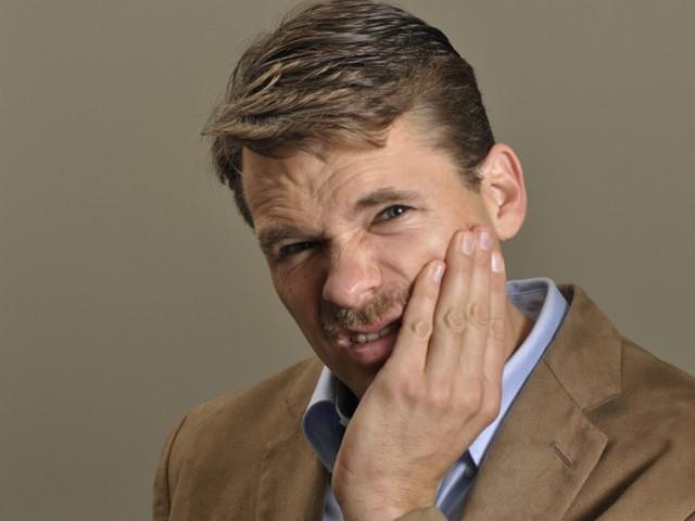 Мужчина страдает болью в челюсти при артрозе внчс